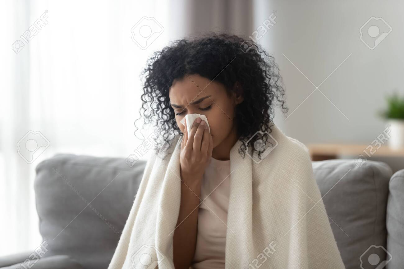Sick African American woman covered warm blanket blowing running nose, feeling bad, suffering from fever, holding handkerchief, allergic reaction or seasonal infection, problem with health - 133473030
