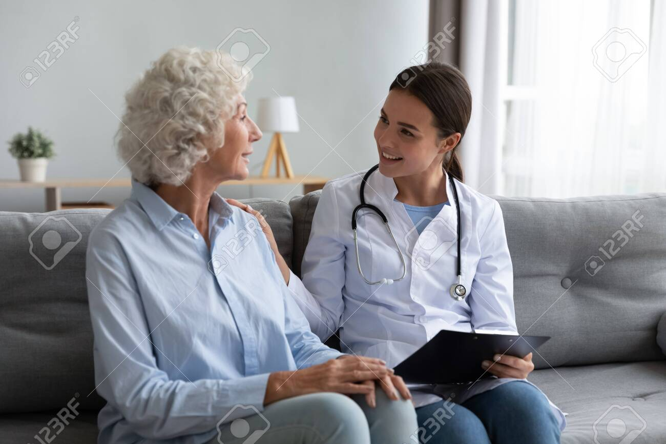 Caring young woman nurse help old granny during homecare medical visit, female caretaker doctor talk with elder lady give empathy support encourage patient sit on sofa older people healthcare concept - 133881750