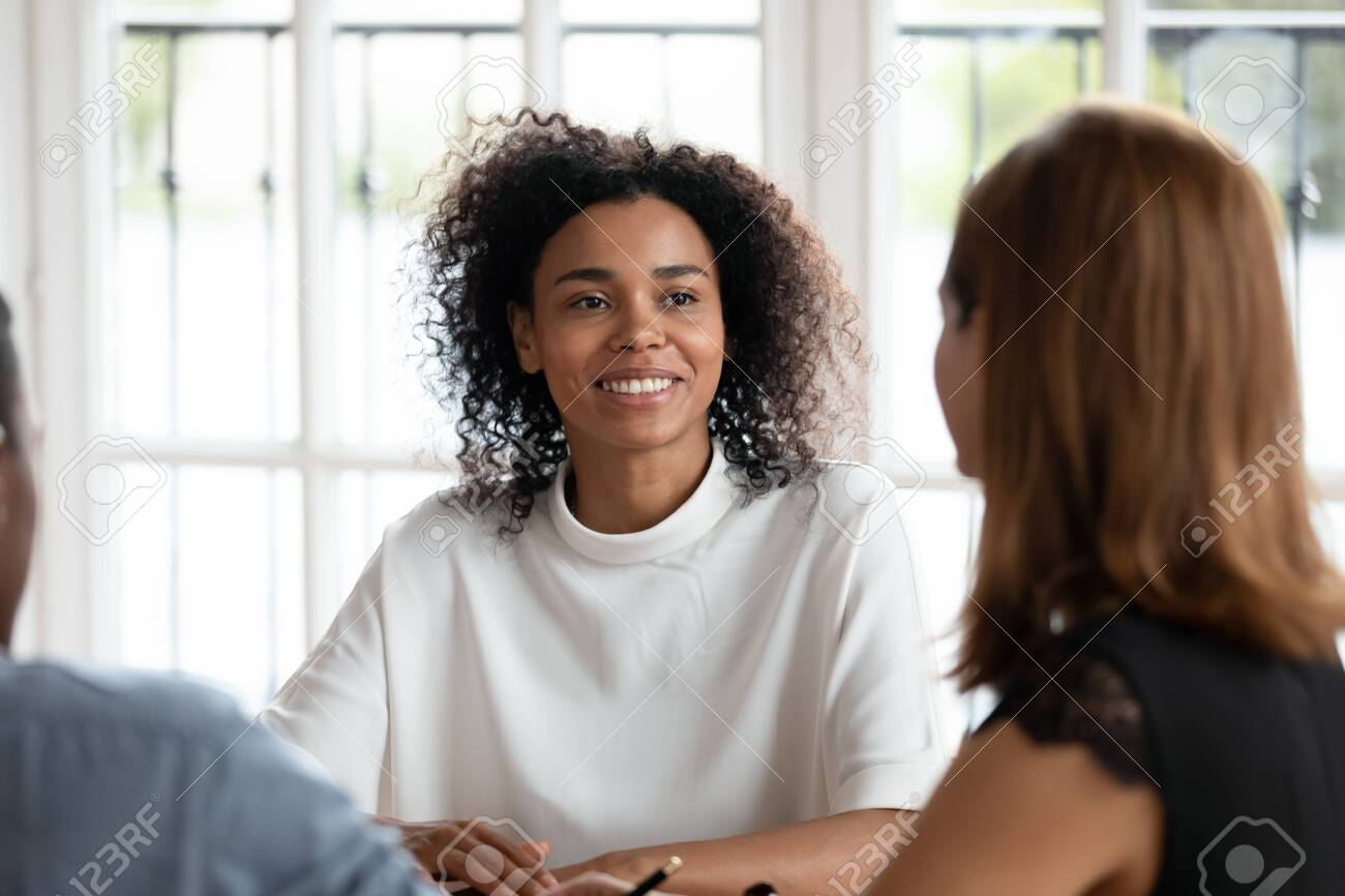 Smiling african american young businesswoman talking with diverse clients or partners at business meeting in office. Happy mixed race female hr manager conducting job interview with applicants. - 134069075