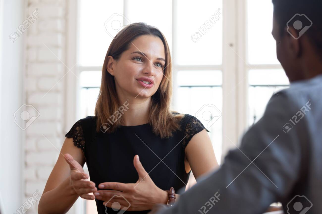 Head shot focus on happy pleasant young female financial advisor realtor lawyer explaining contract details to concentrated thoughtful african american male client at meeting in company office. - 134069158