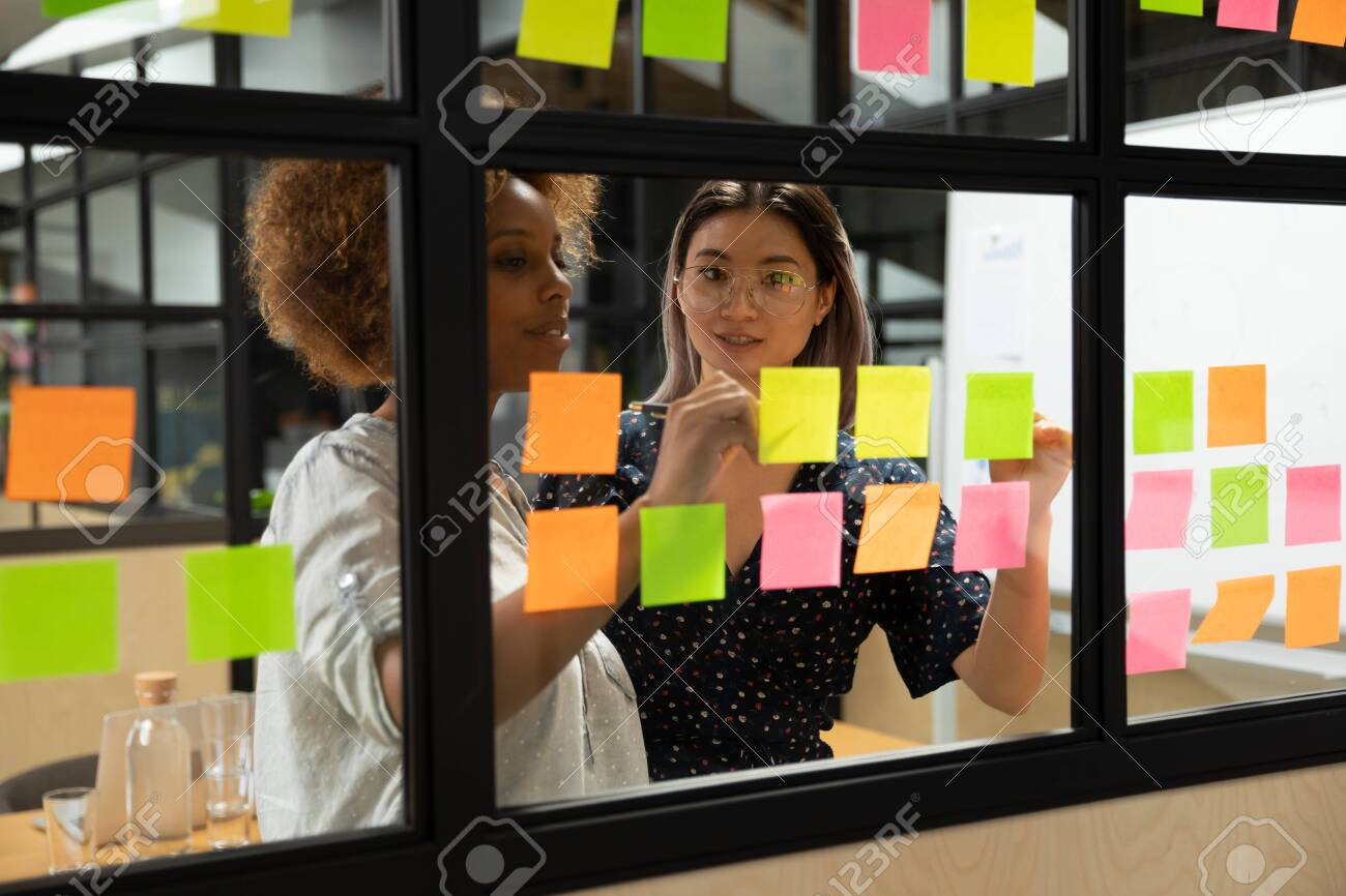 Concentrated african american young female scrum master working together with smart vietnamese businesswoman colleague, putting notes on sticky paper at window glass agile kanban board at office. - 133969051