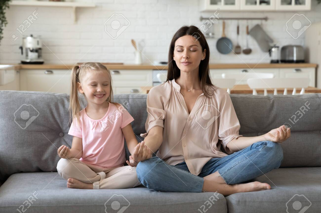 Front view mindful calm 30s woman sitting in lotus pose with cute little daughter on comfortable sofa in living room. Smiling preschool girl practicing yoga breathing exercises with mommy at home. - 133969161