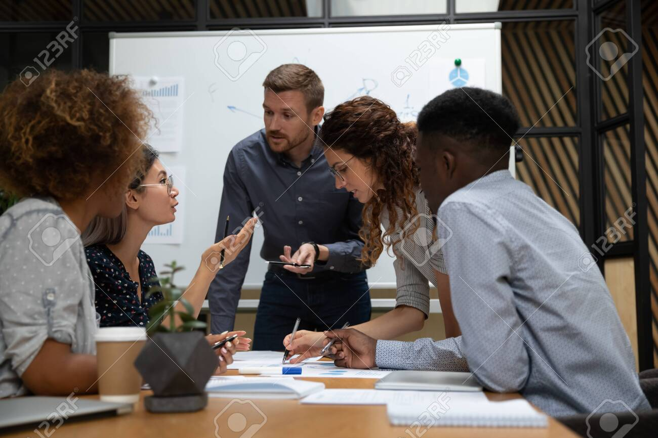 Busy millennial group of motivated mixed race teammates leaning over table at boardroom, discussing first startup project results, negotiating business development marketing strategy together. - 133969222