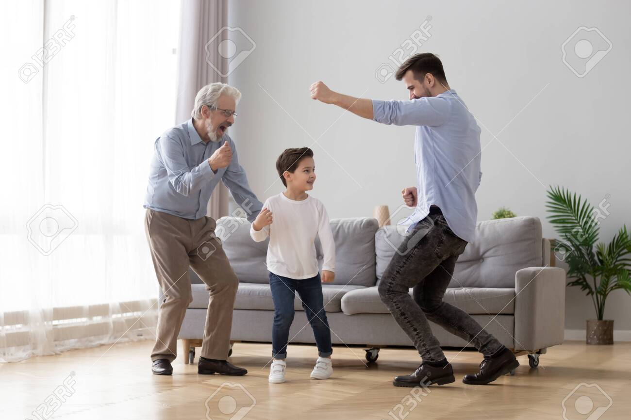 Happy grandfather, father and little son having fun at home, excited granddad, dad and preschool child boy grandchild dancing to favorite music together, family playing in living room, funny activity - 134149265