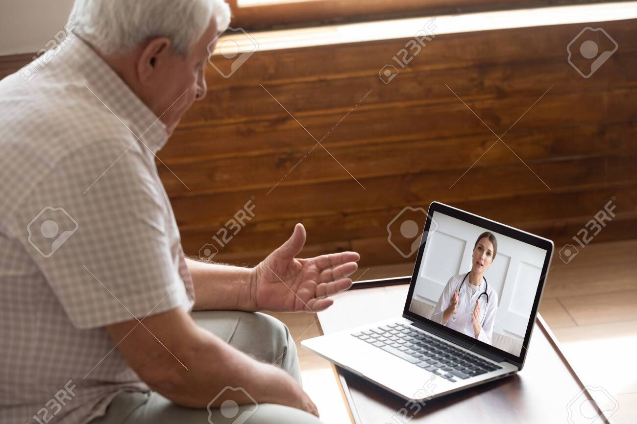 Focused older 80s male patient consulting with doctor via computer video call. Senior man looking at laptop screen, talking to therapist cardiologist online, older generation using modern technology. - 134207607