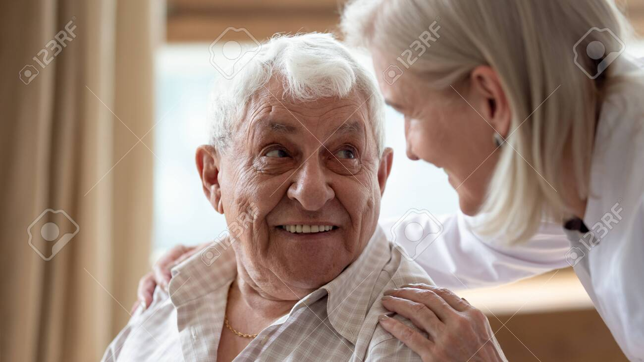 Head shot close up cheerful elderly man looking at pleasant middle aged nurse. Mature female doctor embracing shoulders, communicating with smiling 80s patient, giving support and psychological help. - 134207654
