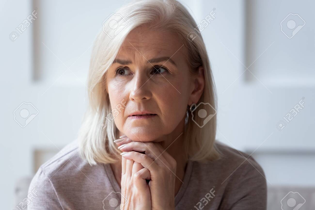 Head shot close up portrait thoughtful middle aged retired woman worrying about personal health problems. Upset older female retiree thinking of family troubles, feeling lonely, sitting at home. - 134207663