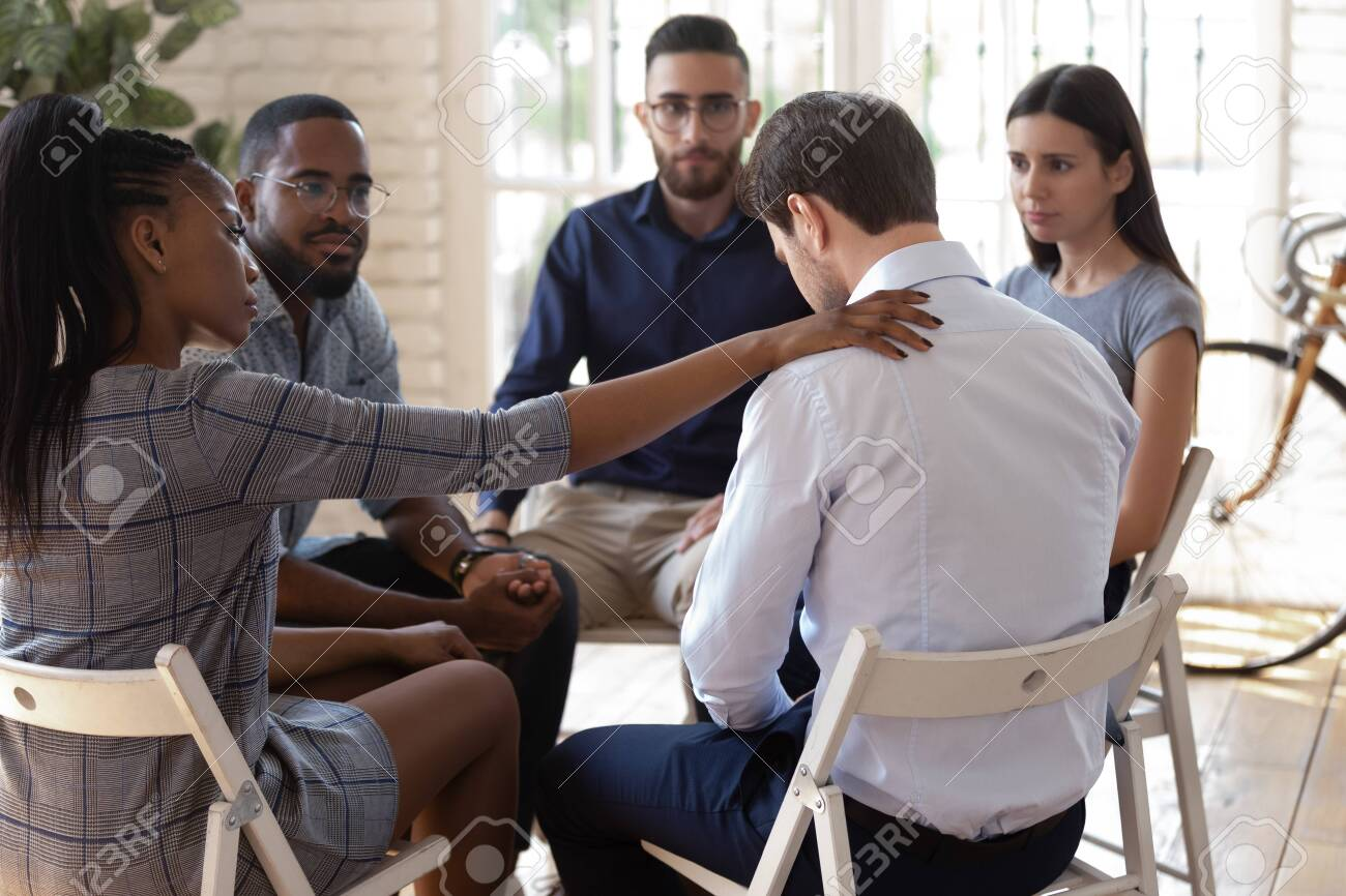 Compassionate african american female employee putting hand on desperate coworkers shoulder, supporting, expressing condolence. Mixed race diverse team of workers sitting in circle on group therapy. - 134421109