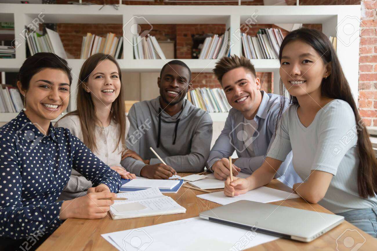 Happy mixed race students gathered in classroom, looking at camera. Smiling group of diverse young people holding video call lecture with abroad online course professor, ready to write down notes. - 135089052