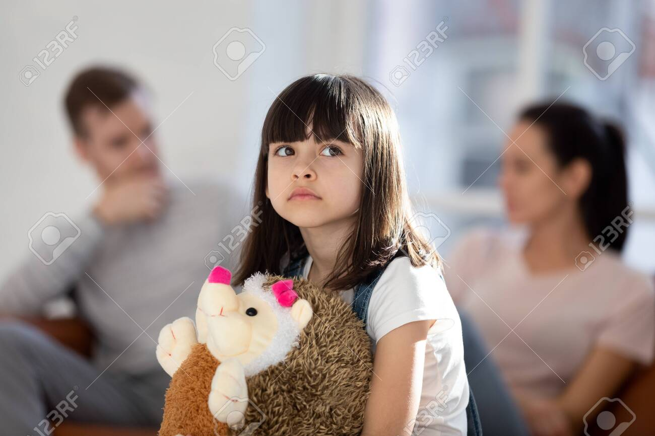 Sad little girl feel upset lonely hug fluffy toy hedgehog friend affected by parent fight or quarrel, upset small child loner stressed with mom and dad divorce or split, family problems concept - 134439499