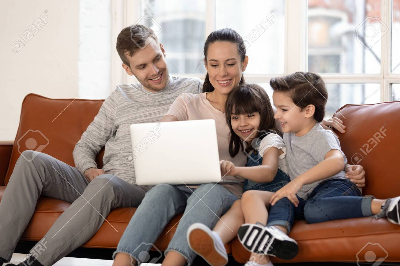 Happy young family with cute preschooler kids have fun at home watching movie on laptop together, loving parents and little children relax in living room smile enjoying cartoon on computer - 134439478