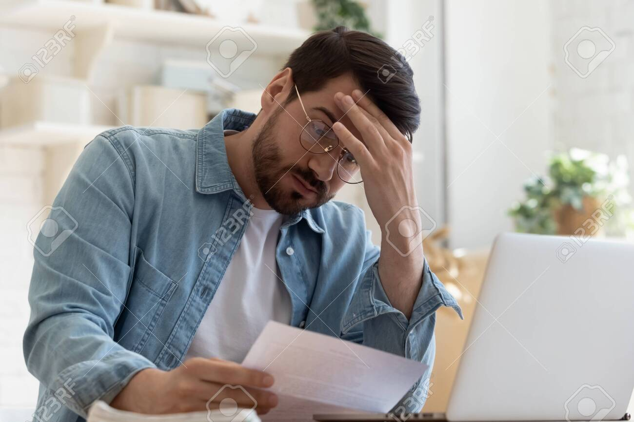 Upset frustrated young man reading bad news in postal mail letter paper document sit at home table, depressed stressed guy worried about high bill tax invoice, overdue debt notification money problem - 134601874