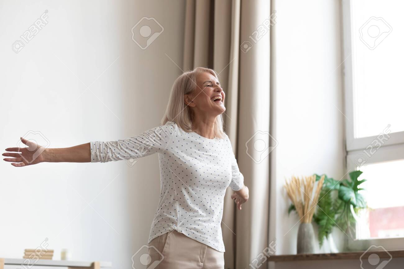 Laughing carefree middle-aged woman standing in living room stretched hands closed eyes breathing fresh air feels happy healthy, starts new day positive mood and thoughts, dancing enjoy life concept - 134587992