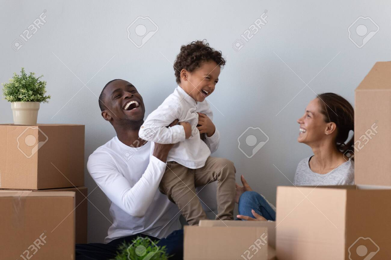 Happy laughing african american young man rising up joyful mixed race cute little son, having fun with wife. Overjoyed smiling multiracial family playing near carton packages, moving in first home. - 134588030