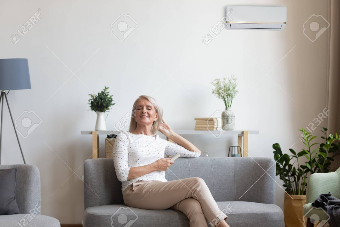 50s woman rest on couch closed eyes enjoy fresh air hold remote control use air conditioner cools herself at summer hot day adjusting temperature inside of living room, comfort wellbeing life concept - 134588037