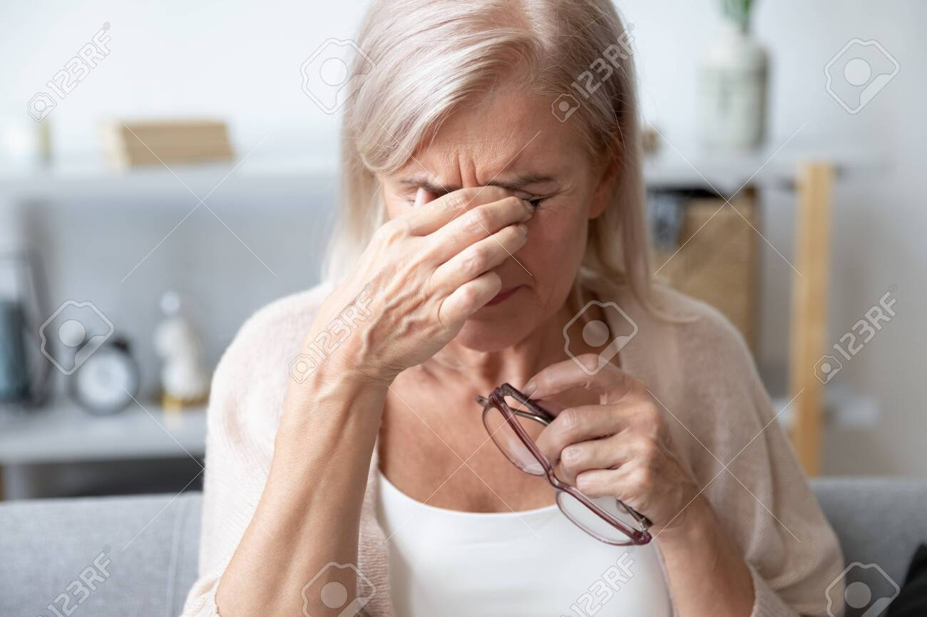 Elderly woman crying wipes tears with hands feels unhappy, bad news. Middle-aged woman taking off glasses closed eyes rubbing eyelid suffers from eye strain deterioration eyesight with age concept - 134588062