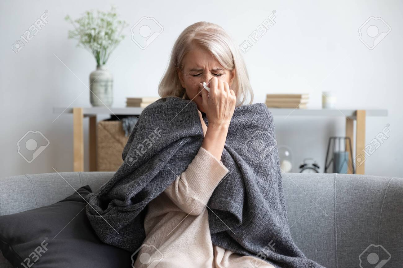 Middle-aged 50s sick frozen woman seated on sofa in living room covered with warm plaid sneezing holding paper napkin blow out runny nose feels unhealthy, seasonal cold, weakened immune system concept - 134588245