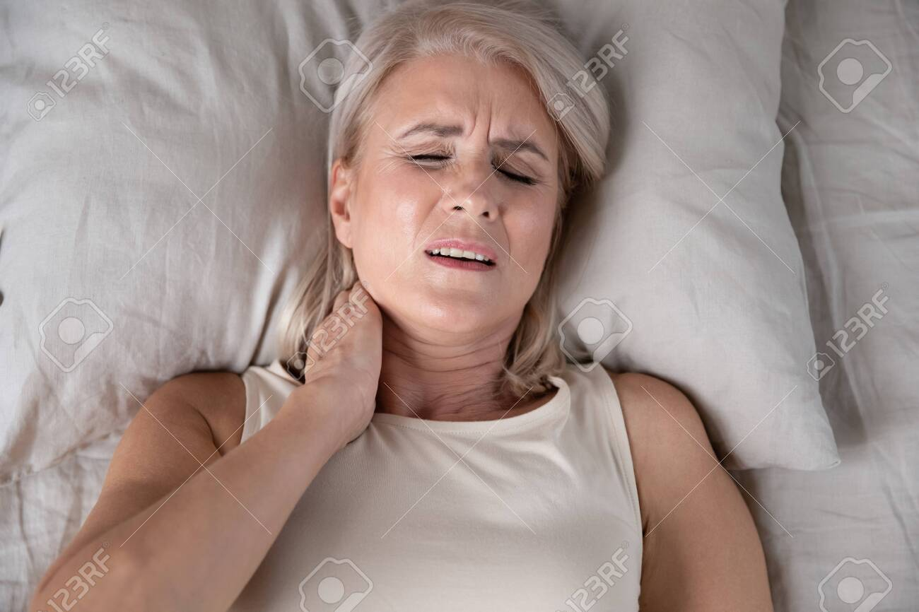 Top close up view middle-aged woman lying in bed in morning feels pain in neck after night sleep, awaken having painful sudden ache or stiffness, incorrect posture during asleep, soft mattress concept - 134588252
