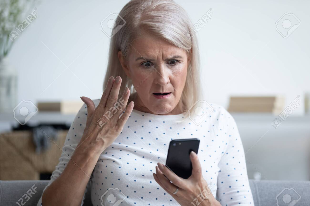 Elderly 50s woman sitting on couch in living room holding smart phone gesturing looking annoyed feels angry having problem with gadget, slow internet, connection lost, discharged broken device concept - 134588473