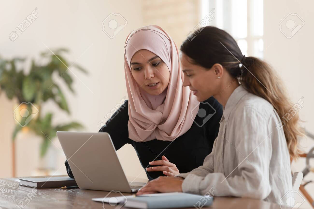 Concentrated young arabian woman in hijab sitting with smiling colleague at table, looking at computer screen, explaining new company software. Focused team leader training millennial female intern. - 134942558