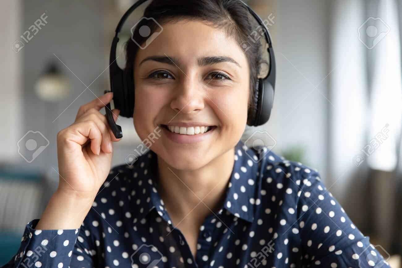 Smiling indian girl teacher counselor telesales agent wear wireless headset look at camera webcam, distance teaching, customer support service concept, telemarketing professional closeup portrait - 137224546