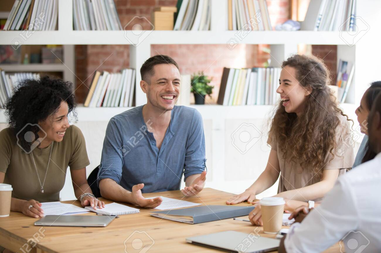 Happy multiracial millennial people sit at shared office desk laugh joking at casual team meeting, smiling diverse colleagues have fun talking chatting at work briefing. Cooperation, teamwork concept - 137892968