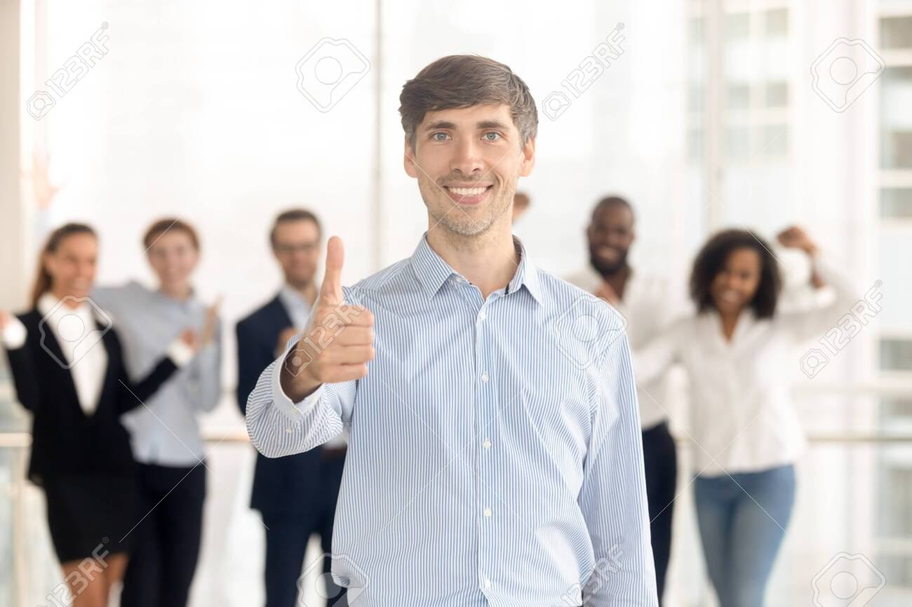 Happy Caucasian man employee or leader stand front show thumbs up recommending company service, smiling male client look at camera give recommendation, excited team support motivate at background - 137893707