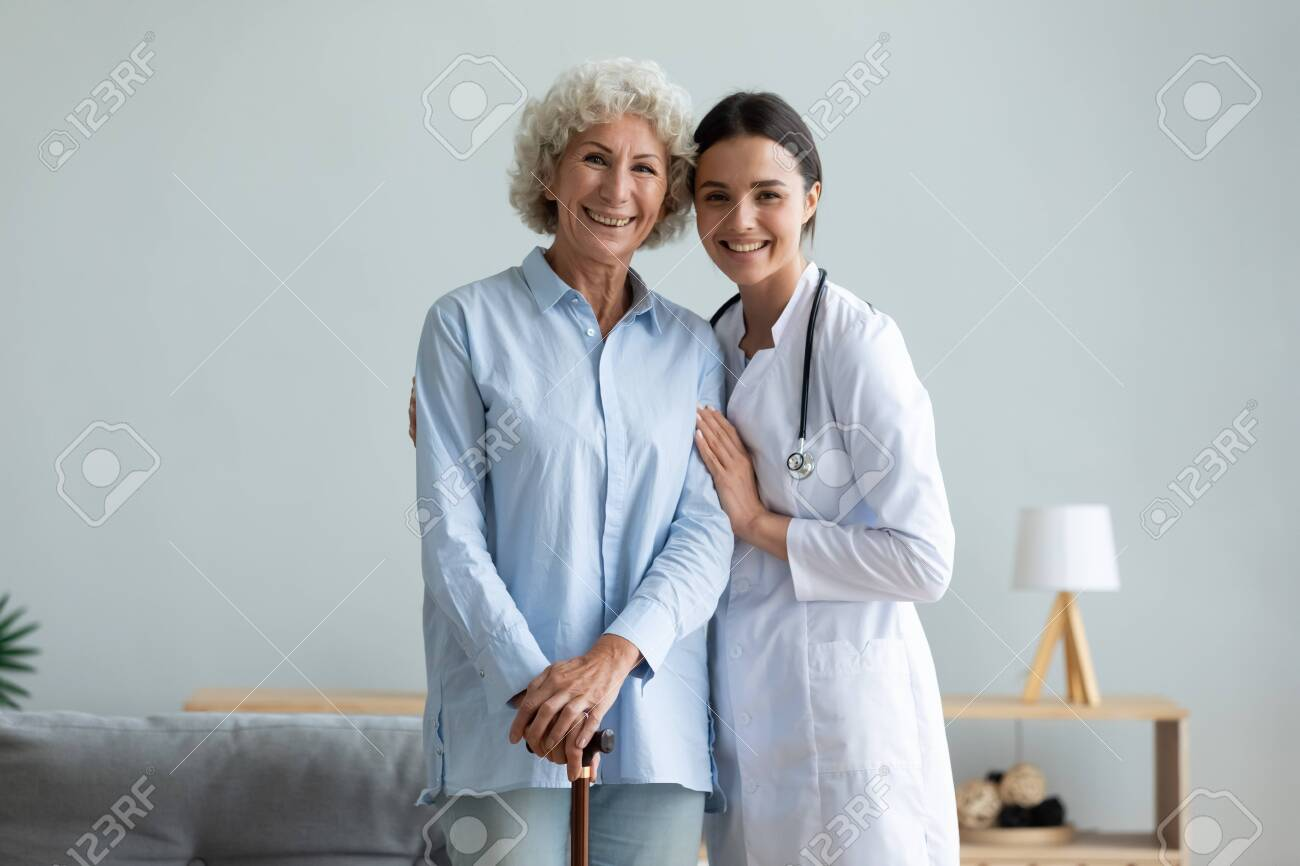 Portrait smiling caregiver and older woman with walking cane standing at home, caring doctor wearing white uniform coat hugging, supporting mature female patient, looking at camera, healthcare - 138135582