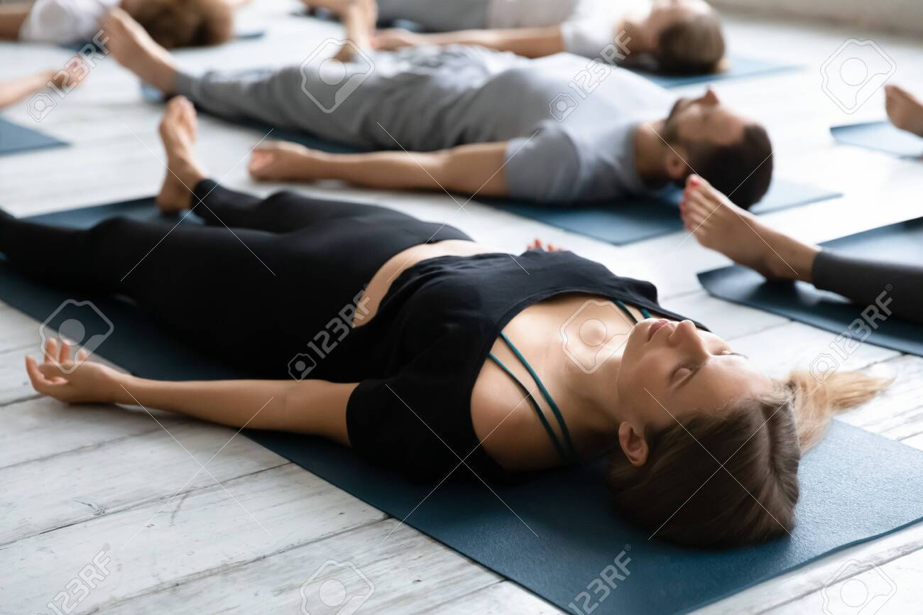 Beautiful young woman meditating in Savasana pose on floor close up, practicing yoga at group lesson, doing Corpse exercise on mats, training, working out in modern yoga studio, center - 138134929
