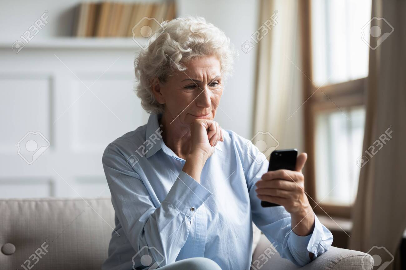 Thoughtful middle aged hoary woman sitting on couch, holding smartphone in hands, reading news. Pensive older woman worrying about bank loan debt sms notification, thinking of financial problems. - 138990148