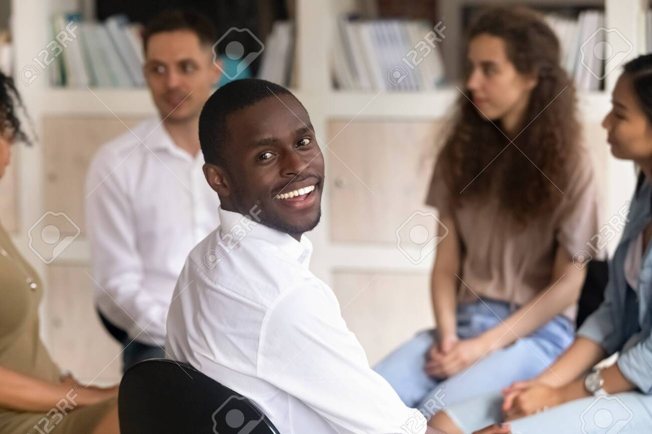 Head shot portrait of smiling African American man sitting at group therapy session, male psychologist looking at camera, coach counselor psychotherapist posing for photo with diverse people - 140686560