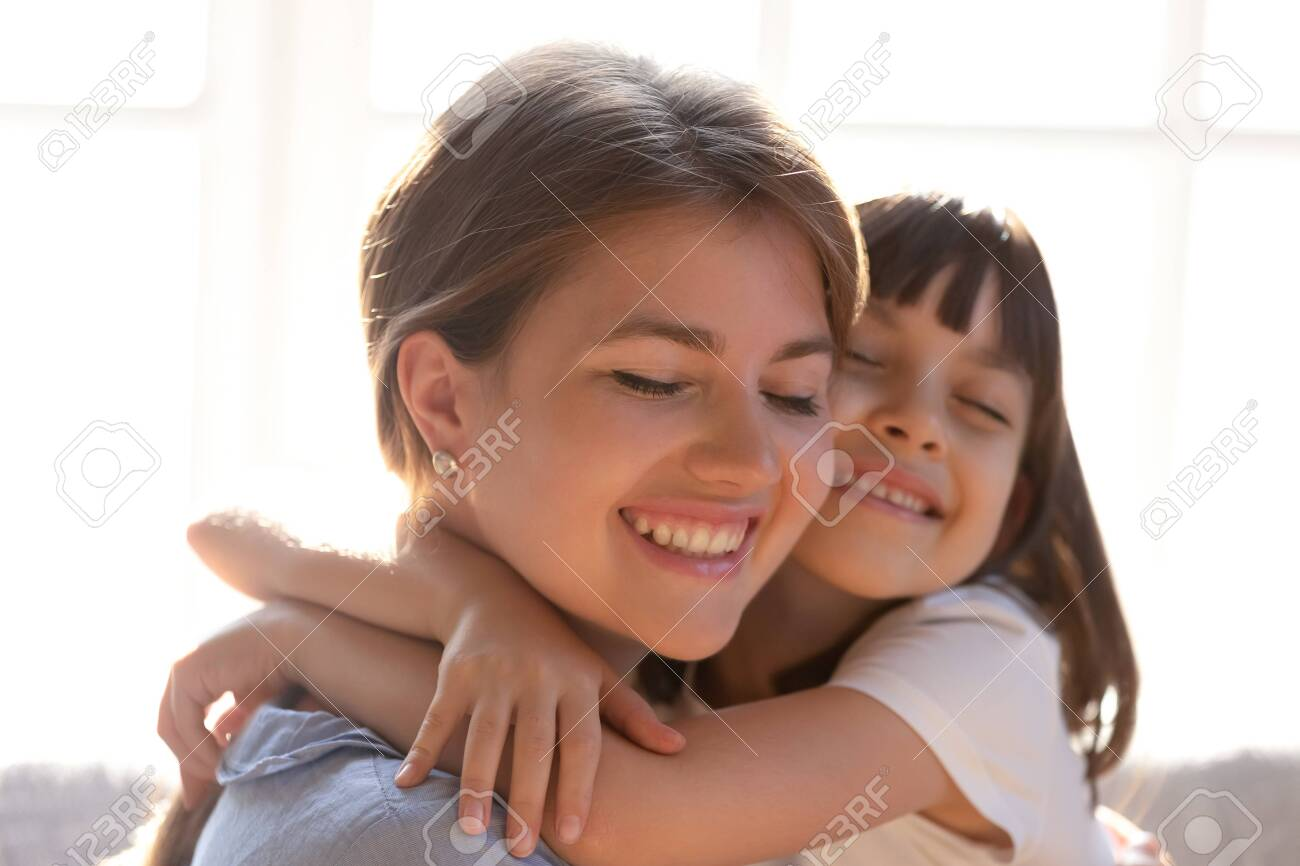 Close up of loving young mom and little daughter hug cuddle showing care and affection, cute small girl child embrace happy mother or nanny, enjoy tender sweet moment at home together - 140874621