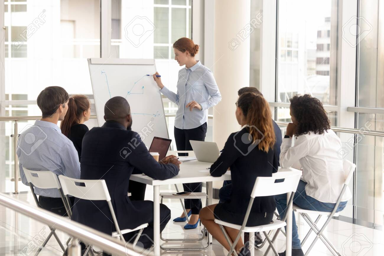 Young female employee with flip chart at presentation. Woman leader consulting diverse group at meeting room, boss mentor coach holds briefing at negotiation, corporate colleague training at boardroom - 141265237