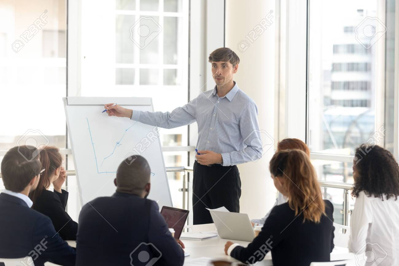Male businessman draws graphs on flip chart at client presentation. Mentor coach talking business report with corporate diverse group at boardroom, leader consulting new project at negotiation room - 141751721
