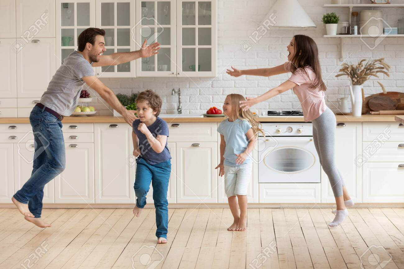 Overjoyed Young Family With Small Kids Entertain In Modern Spacious Stock Photo Picture And Royalty Free Image Image 142502628