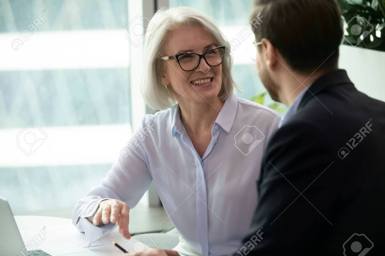 Smiling middle-aged female employee talk brainstorm with male colleague at office briefing in boardroom, happy diverse coworkers have fun laugh cooperating discussing ideas at meeting - 142502694
