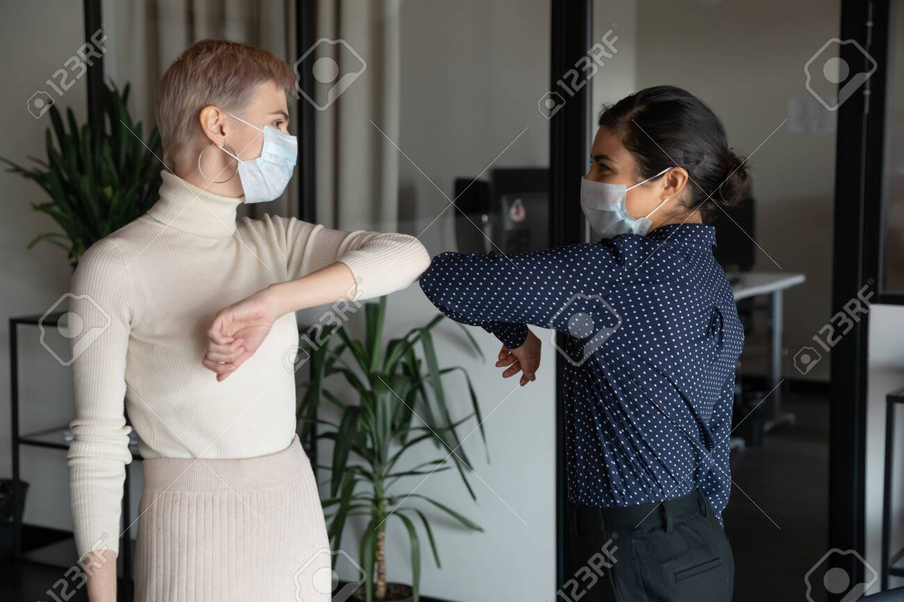 Smiling diverse female colleagues wearing protective face masks greeting bumping elbows at workplace, happy coworkers in medical facial covers protect from COVID-19 pandemics, healthcare concept - 145351859