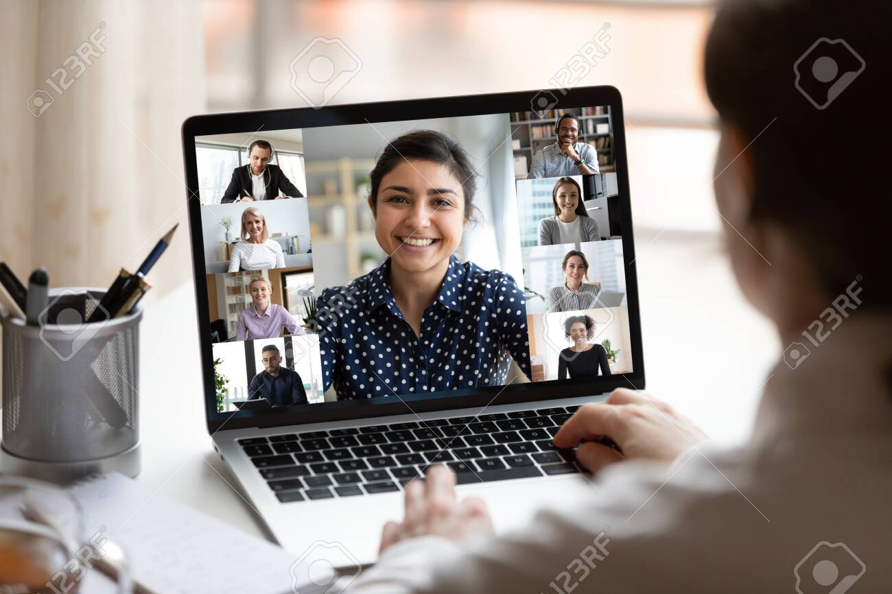 Woman sit at desk looking at computer screen where collage of diverse people webcam view. Indian ethnicity young woman lead video call distant chat, group of different mates using videoconference app - 144657851