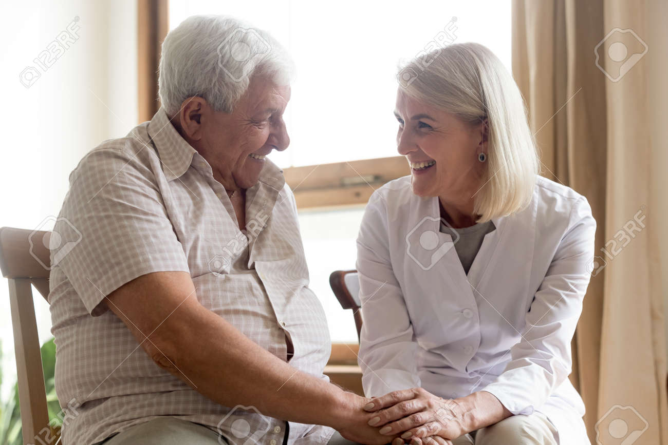 Positive female doctor or nurse hold optimistic senior 80s male patient hands show support and care, woman caregiver medical worker visit consult help mature man, elderly healthcare concept - 146763947
