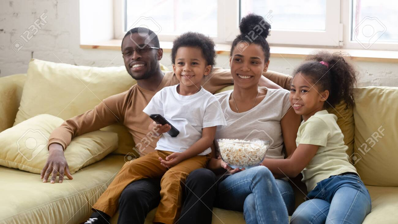 African spouses and little pretty kids spend lazy weekend together seated on couch in living room eating pop-corn choosing show or movie on TV. Happy family activity at home, free time and fun concept - 148168474