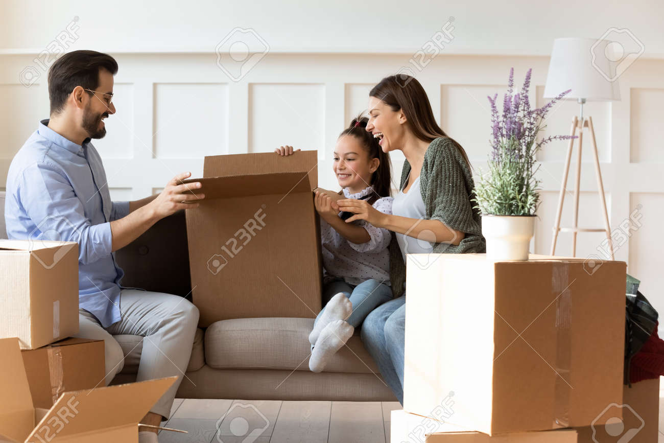 Adorable daughter helping parents with cardboard boxes on moving day, happy family with child sitting on couch, unpacking belongings in modern living room, relocation and mortgage concept - 149841651