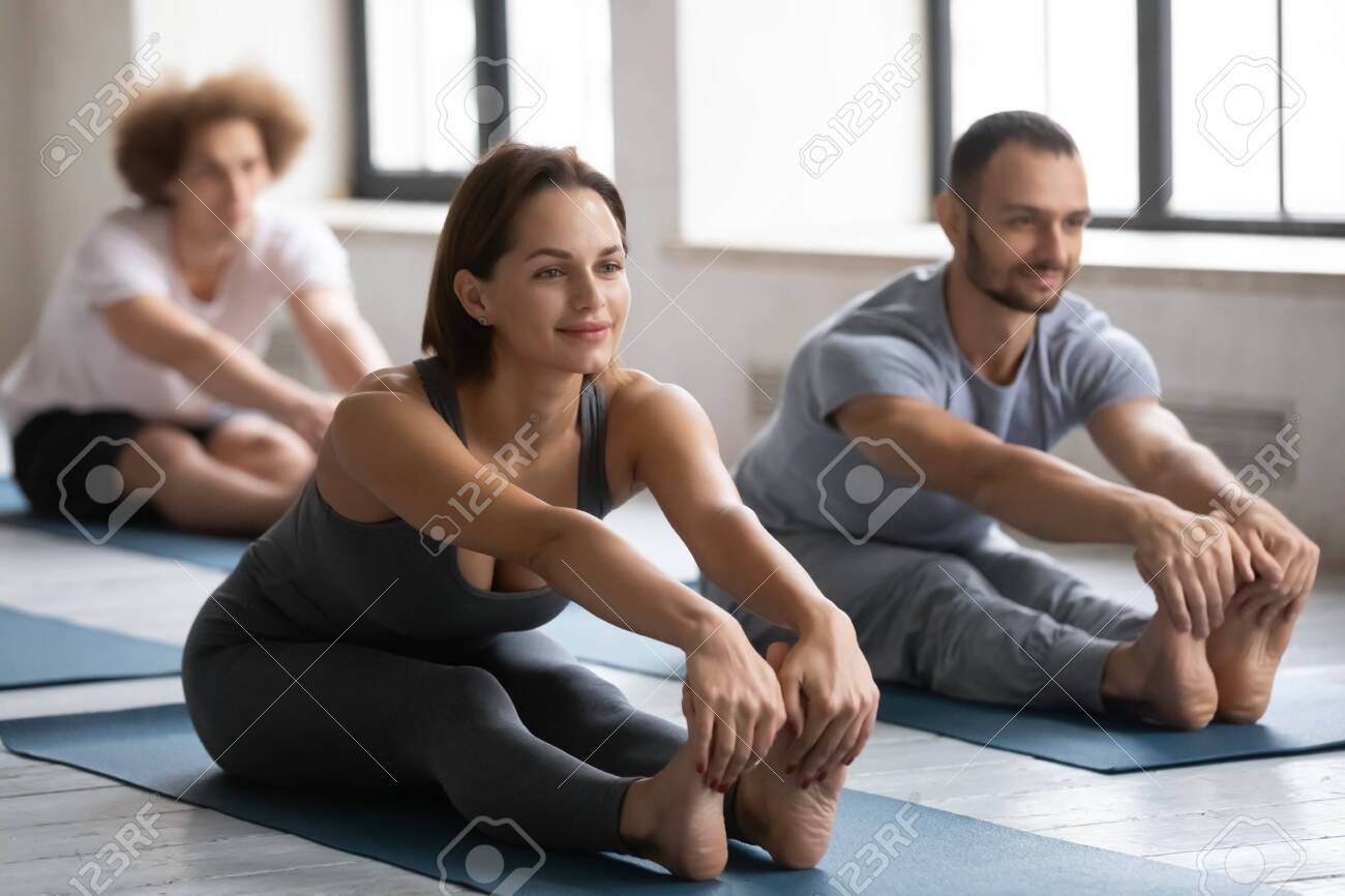 Happy young beautiful european appearance woman touching barefoot toes, stretching back and legs muscles in seated forward bend pose, practicing yoga with friends at group exercise indoors in club. - 150850031