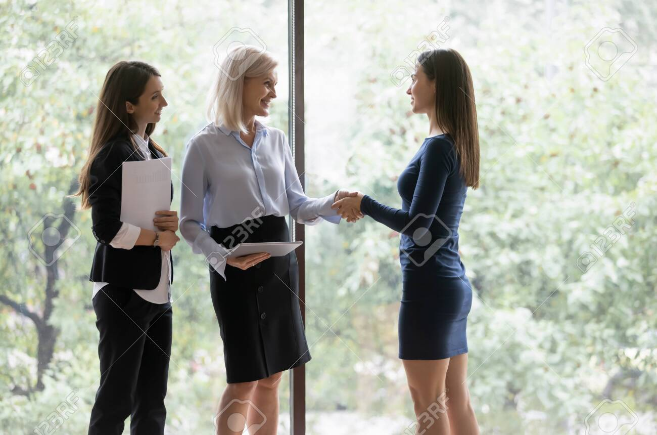 Middle-aged businesswoman greeting millennial female colleague different age business women shake hands express respect smiling, good first impression, hr manager congratulate hired applicant concept - 151918228