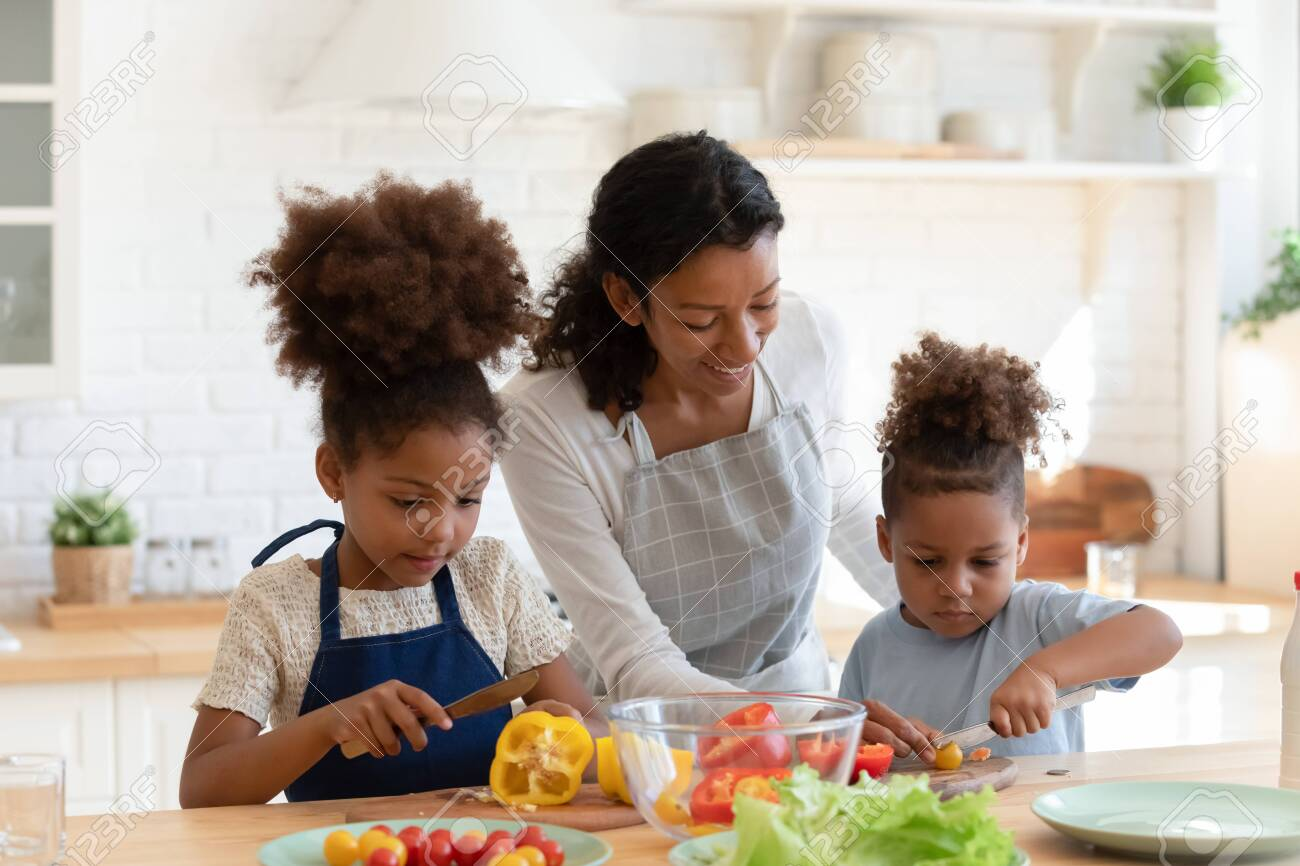 Loving young african American mother or nanny teach little kids prepare healthy food or salad at home kitchen, caring happy biracial mom cooking together with small ethnic children son and daughter - 151824768