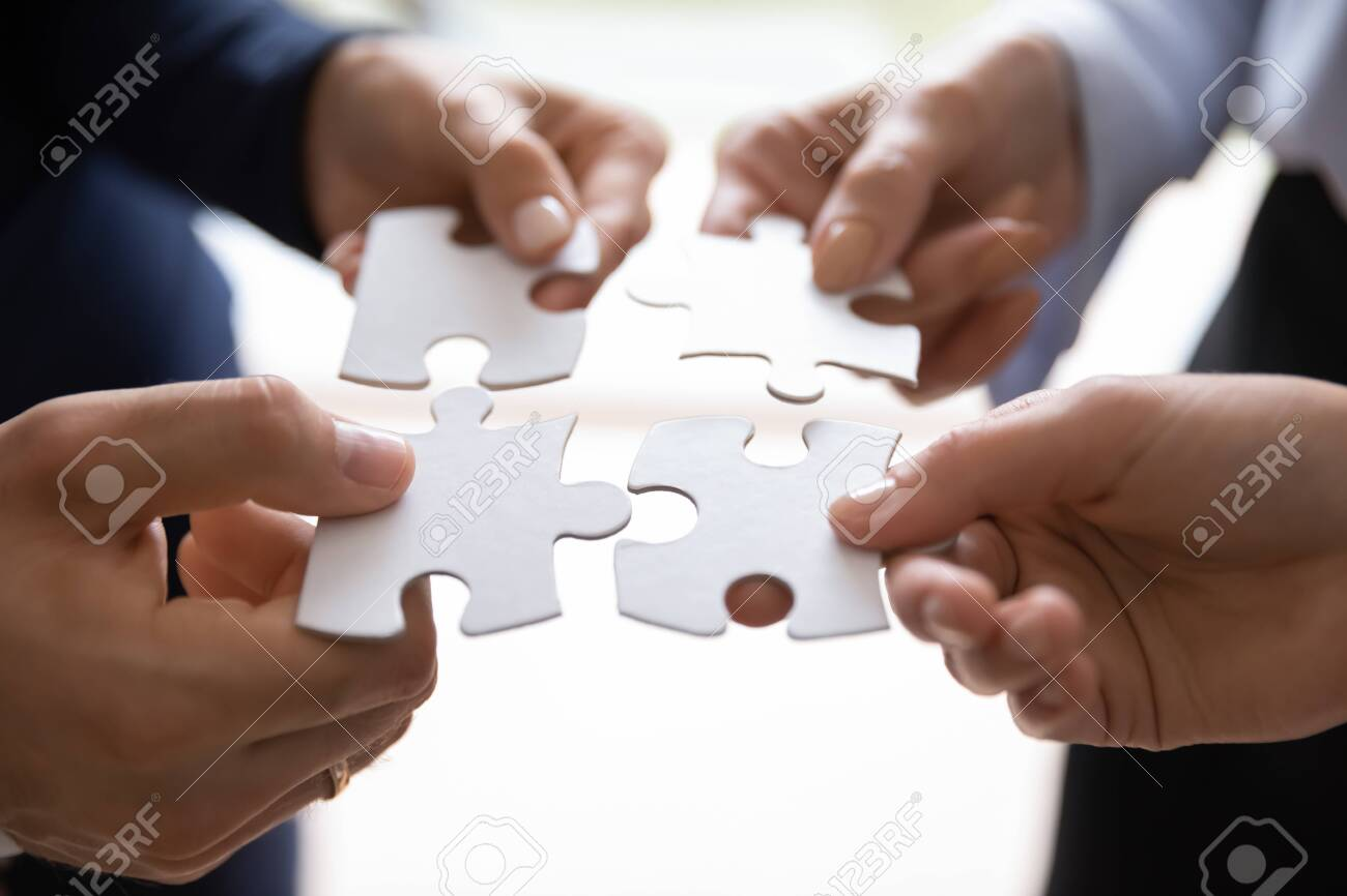 Close up of group of employees colleagues of different age and gender holding pieces of puzzle in hands and uniting them into a single whole. Teambuilding, successful teamwork, mutual support and help - 154160611