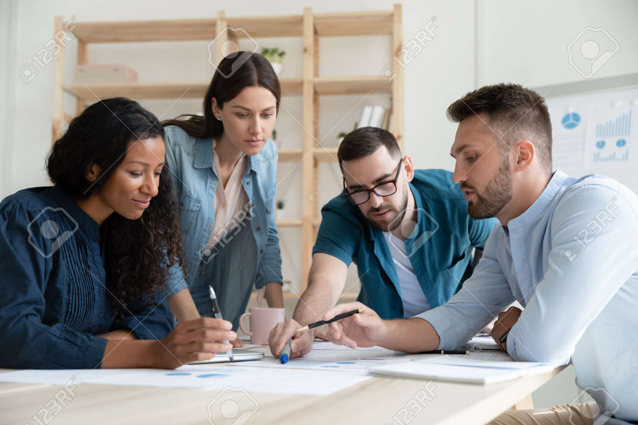 Diverse employees colleagues working with project statistics, financial documents together, sitting at table in modern boardroom, brainstorming at briefing, coworkers group engaged in teamwork - 155565559