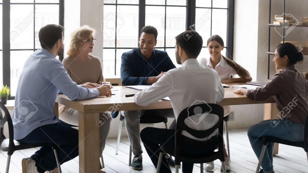 Smiling diverse multiracial businesspeople sit at desk in office discuss ideas at meeting together. Happy multiethnic colleagues have fun laugh brainstorming in group at briefing. Teamwork concept. - 157810987