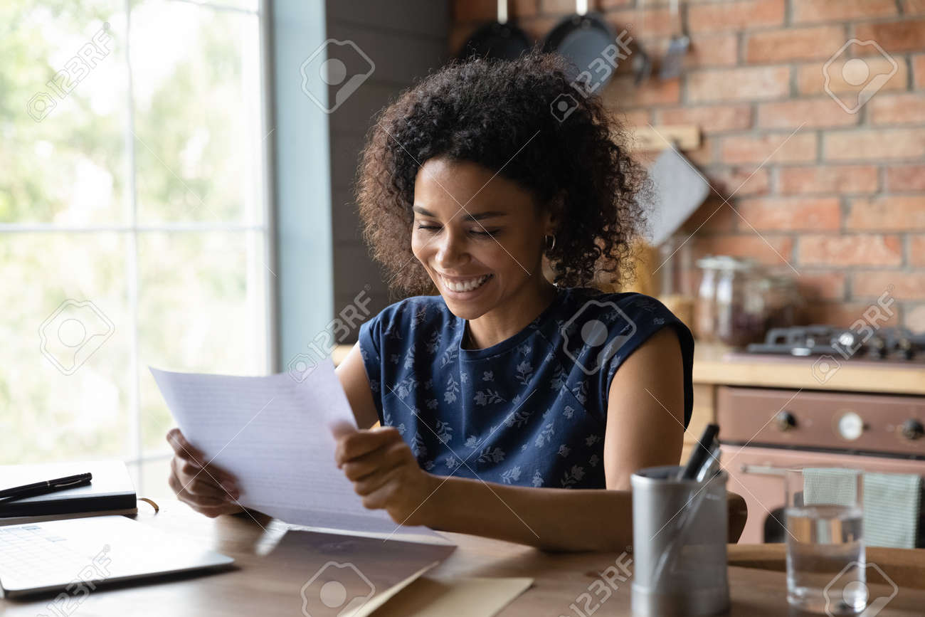 Joyful young mixed race female open paper written letter happy to read positive news from friend. Satisfied self employed black businesswoman get official answer about receiving credit loan from bank - 165791211