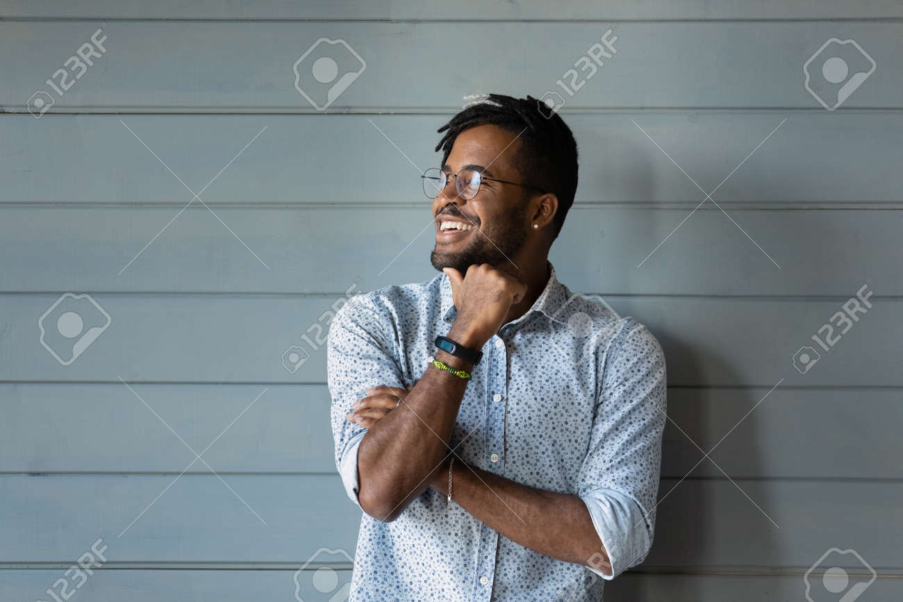 Bearded dreamer. Smiling millennial afro american man hipster in stylish glasses posing against grey wall look away. Confident motivated young black guy dream think feel hopeful optimistic. Copy space - 165791220