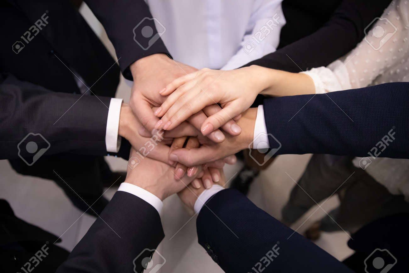 Crop close up top view of multiracial employees colleagues stack hands in pile show team loyalty and unity. Diverse multiethnic businesspeople engaged in teambuilding activity. Teamwork concept. - 167038137
